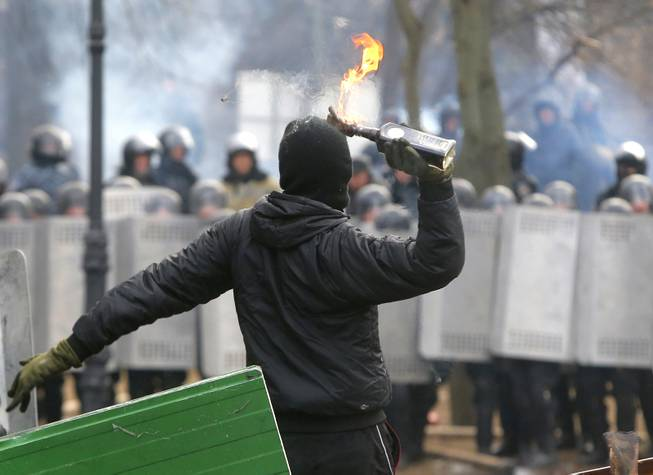 A protester throws a Molotov cocktail during unrest in central Kiev, Ukraine, Monday, Jan. 20, 2014. After a night of vicious streets battles, anti-government protesters and police clashed anew Monday in the Ukrainian capital Kiev. Hundreds of protesters, many wearing balaclavas, hurled rocks and stun grenades and police responded with tear gas.
