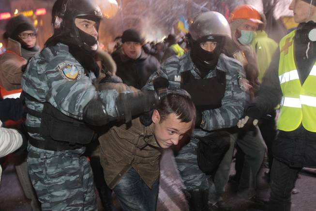 Ukrainian riot policemen pull a Pro-European Union activist out form a tent camps on the Independence Square in Kiev, Ukraine, Wednesday, Dec. 11, 2013. Security forces clashed with protesters as they began tearing down opposition barricades and tents set up in the center of the Ukrainian capital early Wednesday, in an escalation of the weeks-long standoff threatening the leadership of President Viktor Yanukovych.