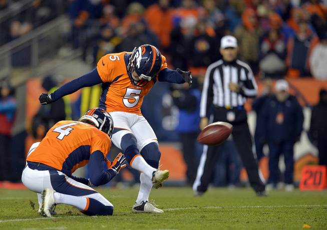 In this Jan. 12, 2014, photo, Denver Broncos kicker Matt Prater (5) kicks an extra point as Broncos punter Britton Colquitt (4) holds during the fourth quarter of an AFC divisional playoff NFL game against the San Diego Chargers in Denver.