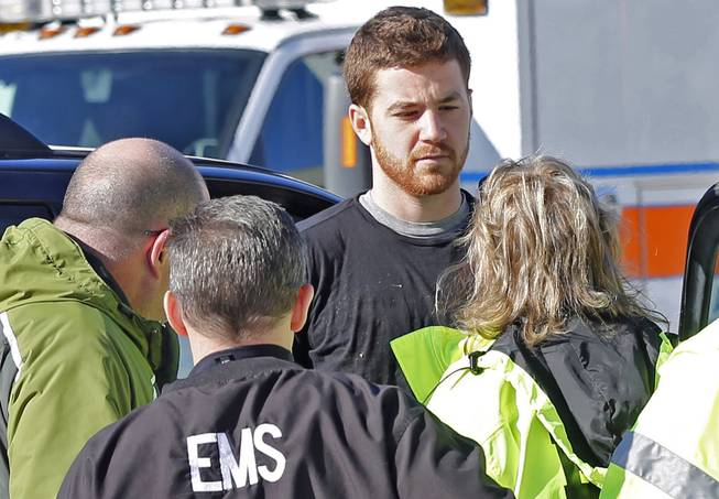 EMS personnel speak with an Cody Cousins, 23, who was detained after a shooting inside the Electrical Engineering building on the campus of Purdue University in West Lafayette, Ind. Cousins, of Warsaw, Ind., is being held in the Tippecanoe County Jail on a preliminary charge of murder, accused of shooting 21-year-old Andrew Boldt of West Bend, Wis.
