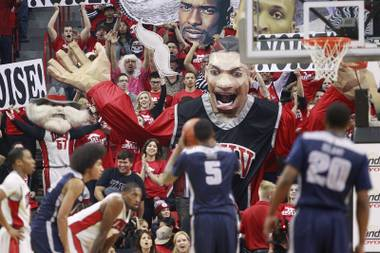 The UNLV student section unveils the giant Khem Kong prop as Utah State center Jarred Shaw shoots a free throw during their game Wednesday, Jan. 22, 2014, at the Thomas & Mack Center.