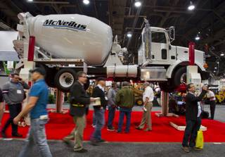 Attendees walk about a mixer above them from a Stertil Koni lift during the 40th anniversary of the World Of Concrete event at the Las Vegas Convention Center on Wednesday, Jan. 22, 2014.