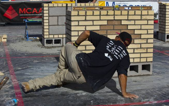 "Jimmy Quinteros of Sarasota, Fl., gets low to inspect his work in the ""Masonry Skills Challenge"" competition as a third year apprentice during the 40th anniversary of the World Of Concrete event on Wednesday, Jan. 22, 2014."