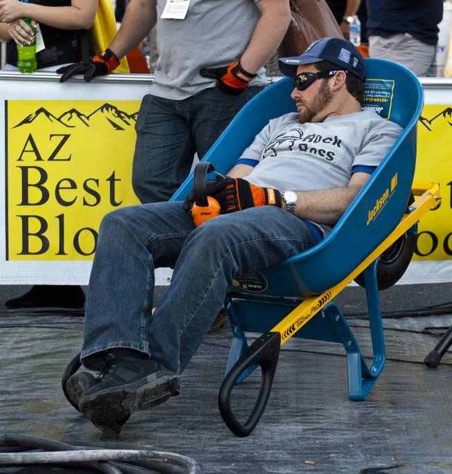"Morgan Agazzi of Livonia, Mich., catches a quick break in a wheelbarrow nearing the finish of the Spec Mix ""Bricklayer 500"" competition during the 40th anniversary of the World Of Concrete event outside the Las Vegas Convention Center on Wednesday, Jan. 22, 2014."