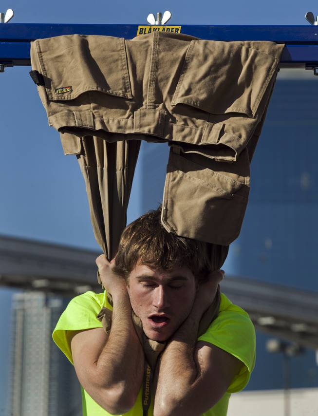 Robert Helfrich of Gahanna, Ohio, hangs from a pair of Blaklader pants during at contest during the 40th anniversary of the World Of Concrete at the Las Vegas Convention Center on Wednesday, Jan. 22, 2014.
