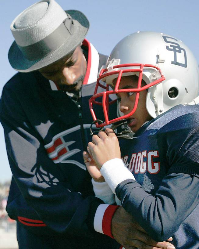 Rap artist and actor Snoop Dogg, left, talks to his son Cordell Broadus, 7, a member of the the Snoop All-Stars youth football team, before their game against the Jacksonville All-Stars in Snoop Bowl at Raines High School in Jacksonville, Fla., Saturday, Feb. 5, 2005.