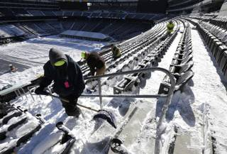 Workers shovel snow off the seating area at MetLife Stadium as crews removed snow ahead of Super Bowl XLVIII following a snow storm, Wednesday, Jan. 22, 2014, in East Rutherford, N.J. Super Bowl XLVIII, which will be played between the Denver Broncos and the Seattle Seahawks on Feb. 2, will be the first NFL title game held outdoors in a city where it snows.