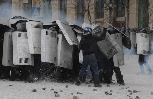 A protester attacks police in central Kiev, Ukraine, Wednesday, Jan. 22, 2014. Police in Ukraineis capital on Wednesday tore down protester barricades and chased demonstrators away from the site of violent clashes, hours after two protesters died after being shot, the first violent deaths in protests that are likely to drastically escalate the political crisis that has gripped Ukraine since late November.
