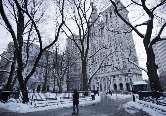 A pedestrian passes through City Hall Park and the Municipal Building, center, Wednesday, Jan. 22, 2014, in New York. The Northeast struggled to dig out of a winter storm Wednesday that swirled up the coast, disrupting government work in Washington and leaving behind bitter cold that sapped fuel supplies.