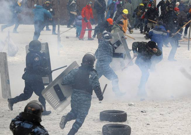 A police officer beats a protester during clashes in central Kiev, Ukraine, Wednesday, Jan. 22, 2014. Police in Ukraineis capital on Wednesday tore down protester barricades and chased demonstrators away from the site of violent clashes, hours after two protesters died after being shot, the first violent deaths in protests that are likely to drastically escalate the political crisis that has gripped Ukraine since late November.