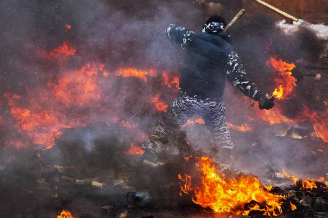 A protester prepares to throw a Molotov cocktail during clashes with police in central Kiev, Ukraine, Wednesday, Jan. 22, 2014. Two people whose dead bodies were found Wednesday near the site of clashes with police have been shot with live ammunition, prosecutors said Wednesday, an announcement that could further fuel violence that spilled on the streets of the Ukrainian capital after two months of largely peaceful protests.