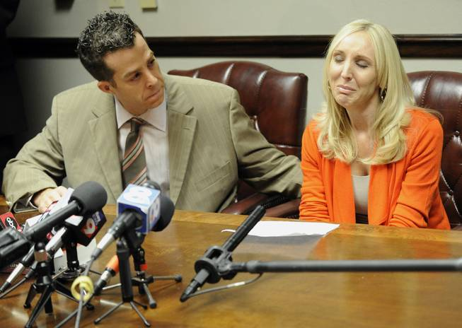 "Nicole Oulson, the widow of Chad Oulson who was shot and killed over a texting dispute at a Wesley Chapel movie theater this month, is consoled by attorney T.J. Grimaldi as she speaks to reporters Wednesday, Jan. 22, 2014, in Tampa, Fla. Oulson became emotional as she read a statement saying her life was ""shattered into a million pieces."""