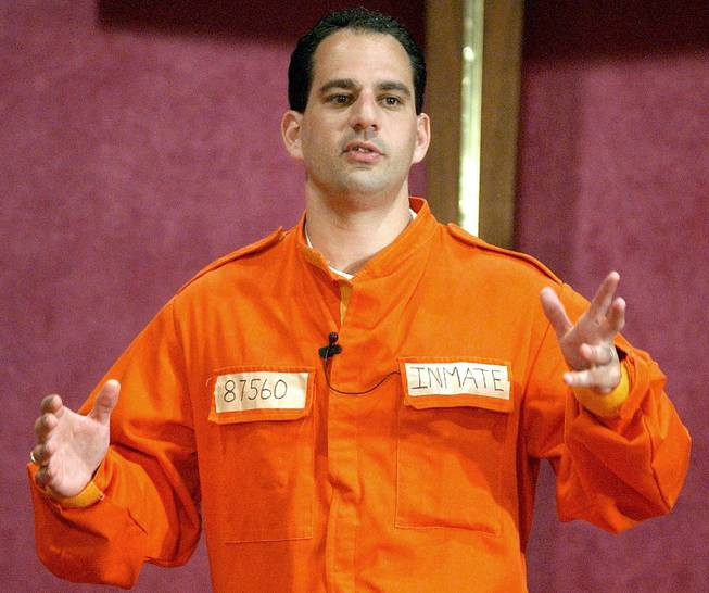 Barry Minkow, a convicted con artist and the co-founder of the for-profit Fraud Discovery Institute, wears a prison jumpsuit costume as he delivers a sermon on materialism at the Community Bible Church in San Diego, July 7, 2002.