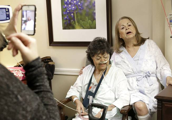 Irma Myers-Santana, left, and her sister Anna Williamson, right, sing a song as Kim Pappas films them with her cellphone in Houston, Jan. 14, 2014. Earlier this month the sisters ended up in the same operating room, each getting one lung from the same donor.