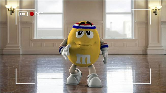 "This image provided by Mars Inc. shows an online teaser ad for M&M's Super Bowl ad featuring its yellow peanut M&M ""spokescandy."""