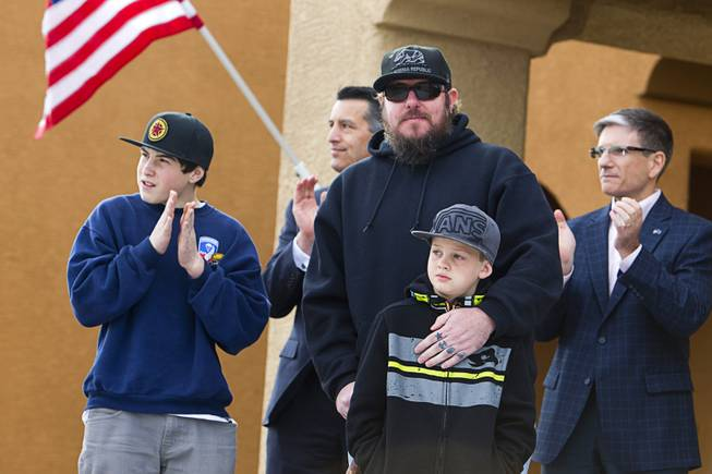 Army Sgt. Christopher Bales, center, and his sons Keenan, 14, and Aiden, 8, listen to speakers during a new home dedication in the Mountain's Edge master-planned community Thursday Jan. 23, 2014. In the background are Nevada Governor Brian Sandoval, left, and Congressman Joe Heck (R-NV).