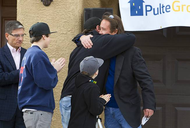 "Stephen Page, right, USAF director of corporate sponsorship for Operation Finally Home, gives a hug to Army Sgt. Christopher Bales during a new home dedication for Bales and his family at the Coldwater Crossing subdivision in the Mountain's Edge master planned community Thursday Jan. 23, 2014. Pulte Homes, along with other companies, presented the home to Bales as part of Operation Finally Home,"" an organization which provides homes to veterans and the families of fallen servicemen."