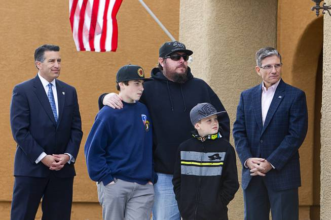"Army Sgt. Christopher Bales, center, and his sons Keenan, 14, and Aiden, 8, listen to speakers during a new home dedication at the Coldwater Crossing subdivision in the Mountain's Edge master planned community Thursday Jan. 23, 2014. Flanking the family are Nevada Governor Brian Sandoval, left, and Congressman Joe Heck (R-NV). Pulte Homes, along with other companies, presented the home to Bales as part of Operation Finally Home,"" an organization which provides homes to veterans and the families of fallen servicemen."