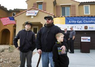 Army Sgt. Christopher Bales, center, and his sons Keenan, 14, and Aiden, 8, talk with reporters in front of their new home at the Coldwater Crossing subdivision in the Mountain's Edge master planned community Thursday Jan. 23, 2014. Pulte Homes, along with other companies, presented the home to Bales as part of Operation Finally Home,