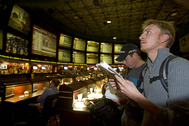 Rufus Peabody, right, of Henderson looks over Super Bowl XLVIII proposition bets were posted on an electronic display board at the Las Vegas Hotel Superbook Thursday Jan. 23, 2014.