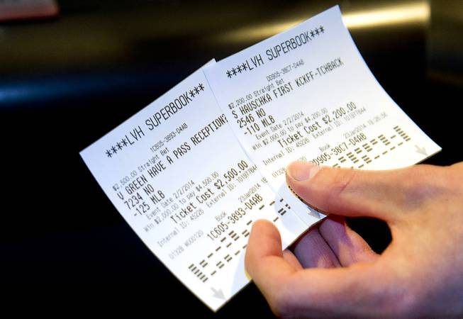 A gambler displays his betting slips after Super Bowl XLVIII proposition bets were posted at the Las Vegas Hotel Superbook Thursday Jan. 23, 2014.