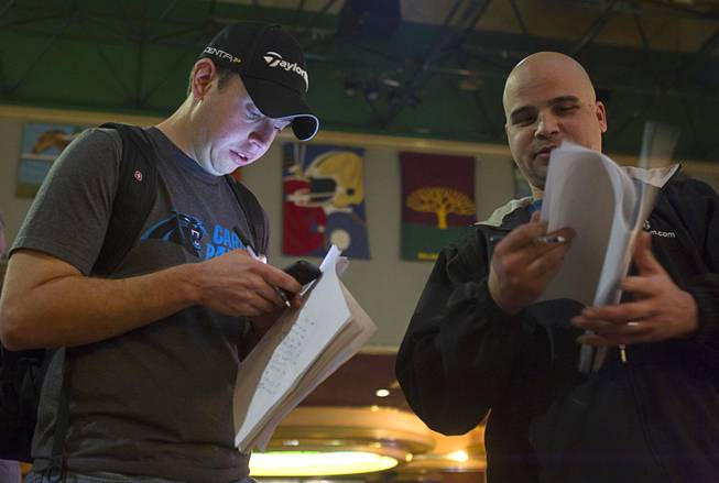 Matt Emanuel, left, of Charlotte, N.C. waits in line to place a bet on Super Bowl XLVIII at the Las Vegas Hotel Superbook Thursday Jan. 23, 2014.