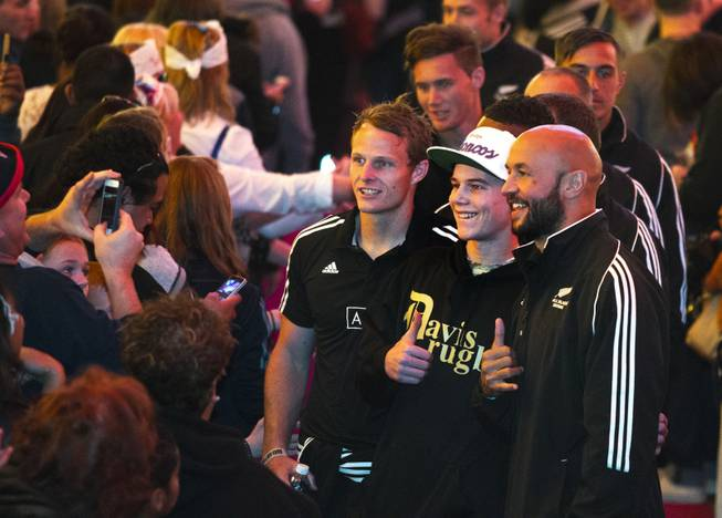USA Sevens International Rugby Tournament players from New Zealand pose with a fan on the red carpet during a parade and opening ceremonies at the Fremont Street Experience on Thursday, Jan. 23, 2014.