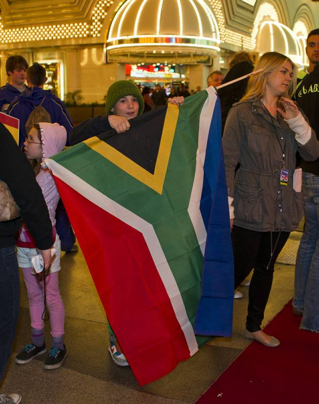 Jackson Bourgon, 11, of Las Vegas unfurls the S. Africa flag he will carry at the opening ceremonies and parade for the USA Sevens International Rugby Tournament  held at the Fremont Street Experience on Thursday, Jan. 23, 2014.