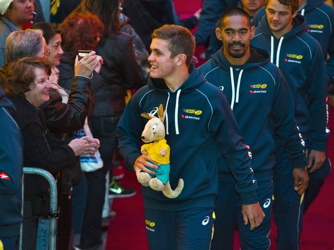 USA Sevens International Rugby Tournament players from Australia, one carrying a stuffed kangaroo, greet fans along the red carpet during a parade to the opening ceremonies at the Fremont Street Experience on Thursday, Jan. 23, 2014.