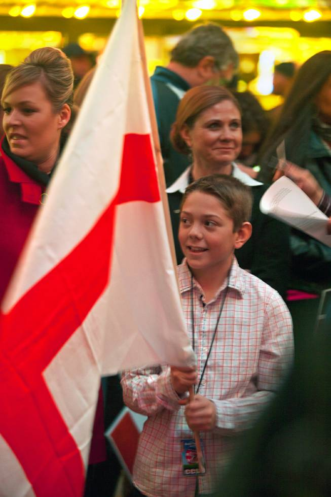 A Clark County School District student carries the team England flag during the opening ceremonies and parade for the USA Sevens International Rugby Tournament at the Fremont Street Experience on Thursday, Jan. 23, 2014.