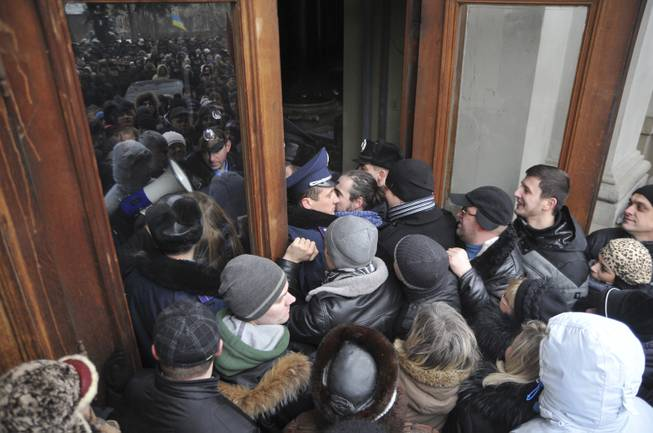 Protesters break into the building of the regional governor's office in Lviv, Western Ukraine, Thursday Jan. 23, 2014. Tensions in Ukraine spread far from its embattled capital on Thursday as hundreds of people in the city of Lviv stormed into the regional governor's office and forced him to write a letter of resignation.