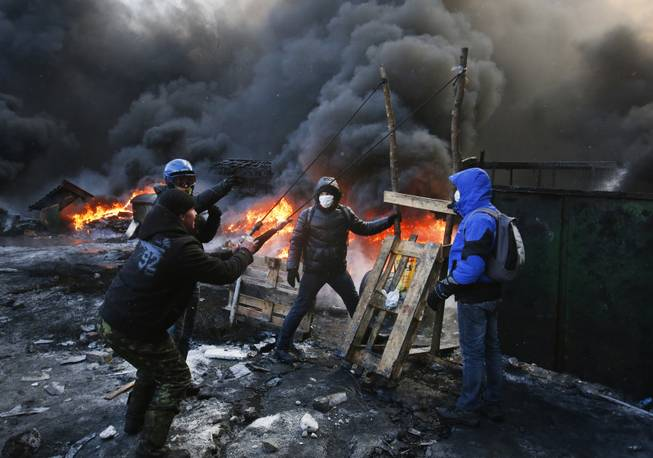 Protesters use a large slingshot to hurl rocks at police in central Kiev, Ukraine, Thursday Jan. 23, 2014. Thick black smoke from burning tires engulfed parts of downtown Kiev as an ultimatum issued by the opposition to the president to call early election or face street rage was set to expire with no sign of a compromise on Thursday. (AP Photo/Sergei Grits)