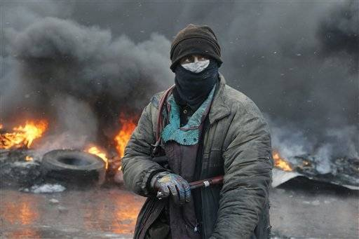 A protester stands at a burning barricades between police and protesters in central Kiev, Ukraine, Thursday Jan. 23, 2014. Thick black smoke from burning tires engulfed parts of downtown Kiev as an ultimatum issued by the opposition to the president to call early election or face street rage was set to expire with no sign of a compromise on Thursday.
