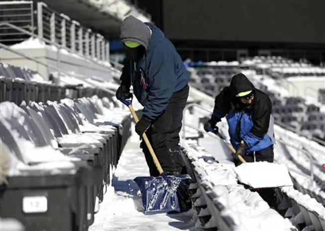 Workers shovel snow off the seates at MetLife Stadium as crews removed snow ahead of Super Bowl XLVIII following a snow storm, Wednesday, Jan. 22, 2014, in East Rutherford, N.J. Super Bowl XLVIII, which will be played between the Denver Broncos and the Seattle Seahawks on Feb. 2, will be the first NFL title game held outdoors in a city where it snows.