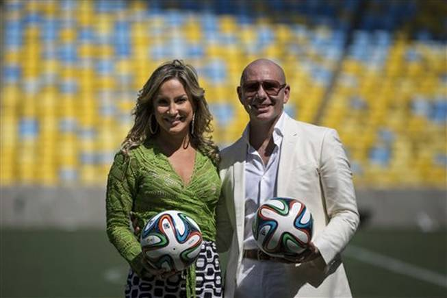 Brazilian singer Claudia Leitte and rapper Pitbull pose for the media during a news conference at the Maracana stadium in Rio de Janeiro, Brazil, Thursday, Jan. 23, 2014. Leitte, along with Jennifer Lopez and Pitbull, will perform the official song for the 2014 World Cup. Football's governing body didn't elaborate when the song, written and co-produced by Pitbull will be released.