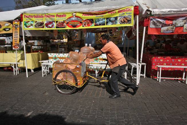 A vendor pushes his bicycle cart filled with 18-liter jugs of bottled water to sell to owners of street food stalls in Mexico City,  Jan. 4, 2014. Bad tap water accounts in part for Mexico being the highest consumer of bottled water and sweetened drinks.
