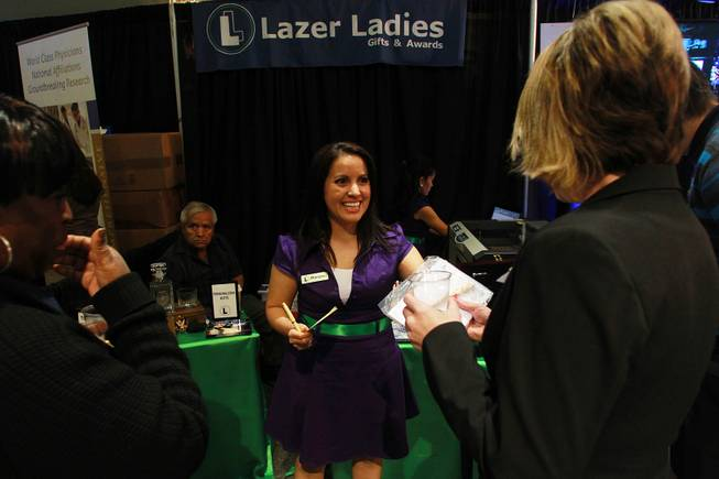 "Marylou Soto, one of the owners of Lazer Ladies Gifts & Awards, hands out custom engraved pens during the Las Vegas Metro Chamber of Commerce ""Preview Las Vegas"" event Friday, Jan. 24, 2014."