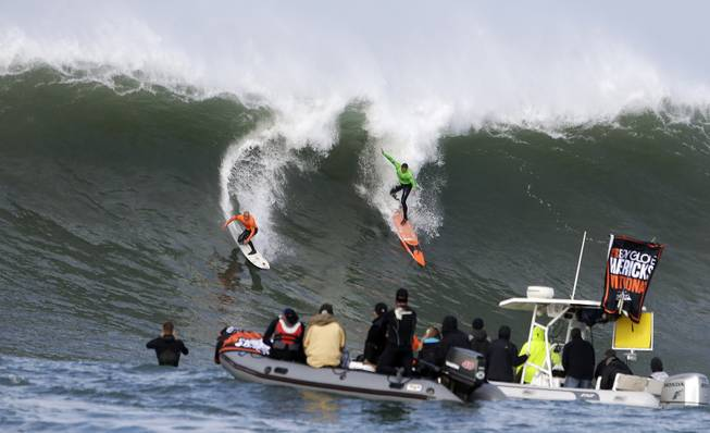 Shane Dorian, left, and Ben Wilkinson, right, catch a wave during the third heat of the first round of the Mavericks Invitational big wave surf contest Friday, Jan. 24, 2014, in Half Moon Bay, Calif.