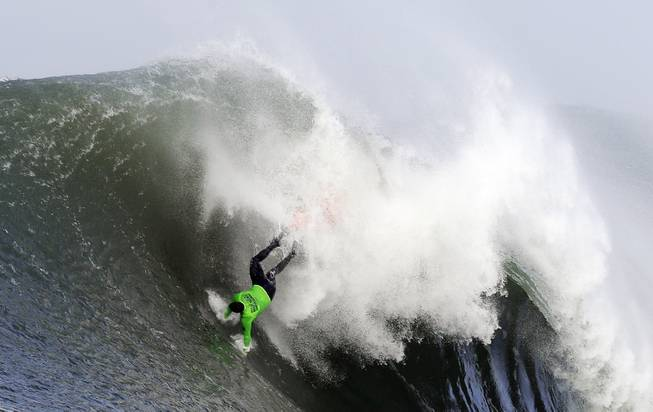 Ben Wilkinson goes tumbling into a wave during the third heat of the first round of the Mavericks Invitational big wave surf contest Friday, Jan. 24, 2014, in Half Moon Bay, Calif.