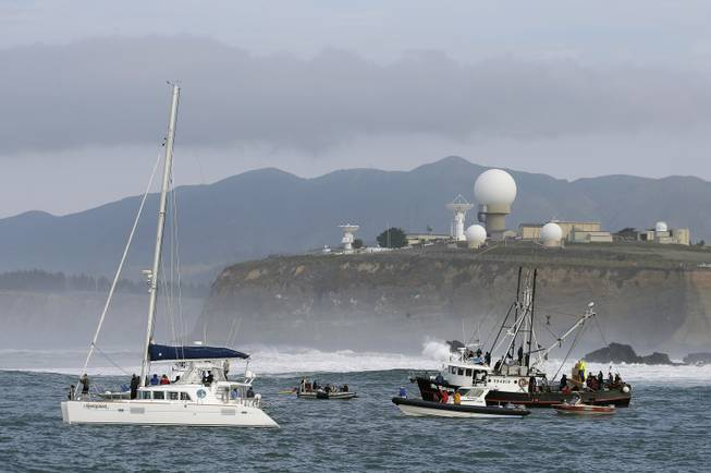 People on boats watch the third heat of the first round of the Mavericks Invitational big wave surf contest with the Pillar Point Air Force Station in the background Friday, Jan. 24, 2014, in Half Moon Bay, Calif.