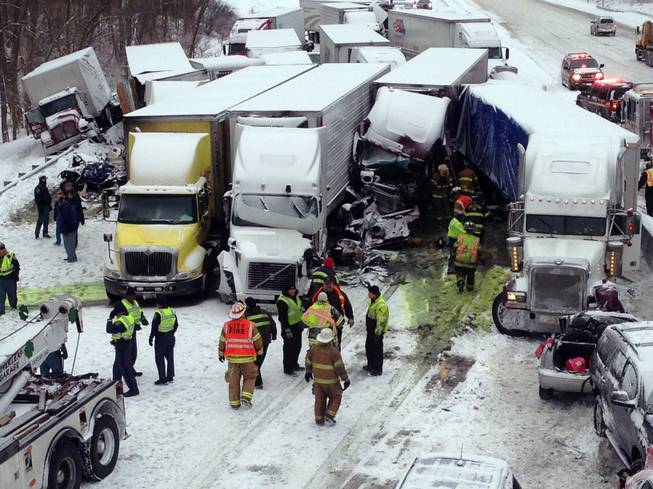 In this photo provided by the Indiana State Police, emergency crews work at the scene of a massive pileup involving more than 40 vehicles, many of them semitrailers, along Interstate 94, Thursday afternoon, Jan. 23, 2014, near Michigan City, Ind. At least three were killed and more than 20 people were injured.