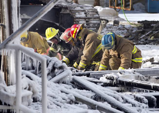 Rescue personnel search through the icy rubble of deadly fire that destroyed a seniors' residence Friday, Jan. 24, 2014, in L'Isle-Verte, Quebec.