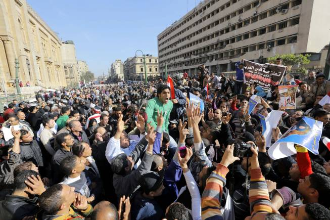 Egyptians shout anti-terrorism slogans as they demonstrate in front the site of a blast at the Egyptian police headquarters, at right, and the Museum of Islamic Art, at left, in downtown Cairo, Egypt, Friday, Jan. 24, 2014. A car bomb struck the main Egyptian police headquarters Friday in the heart of Cairo, killing several people in a hugely symbolic attack on the eve of the third anniversary of the 2011 uprising that toppled longtime autocratic ruler Hosni Mubarak.