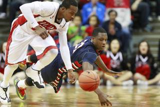 UNLV guard Deville Smith and Fresno St. guard Marvelle Harris chase down a loose ball during their game Saturday, Jan. 25, 2014 at the Thomas & Mack Center. UNLV won 75-73 in overtime.