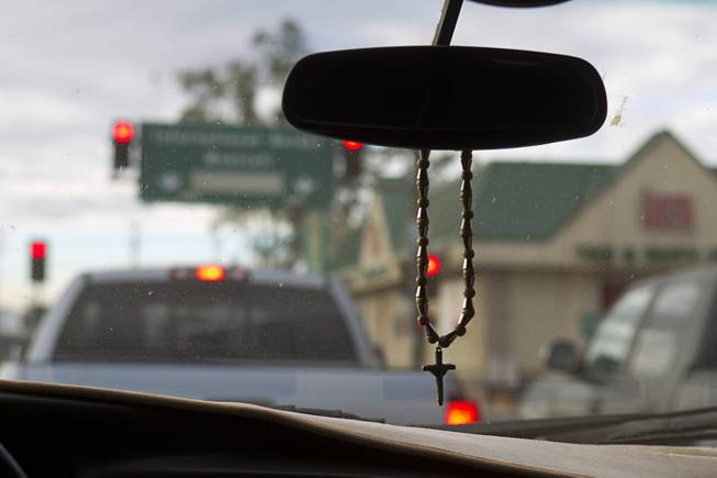 A crucifix hangs from the rear view mirror as the Diaz family prepares to cross the border into Mexicali, Mexico Saturday, Jan. 25, 2014.