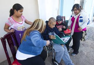 Francisco Diaz, center, looks over a photo album with family members in Mexicali, Mexico Saturday, Jan. 25, 2014. Diaz was born in Mexico but grew up in Las Vegas with a green card.
