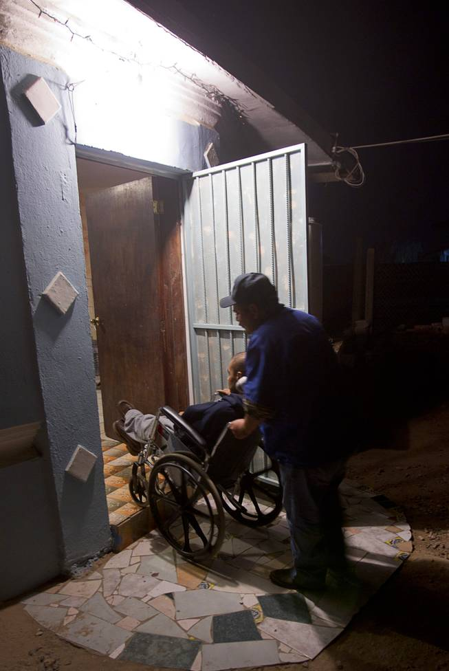 Assistant Jose Alberto Ramirez takes Francisco Diaz back inside a elderly care home in Mexicali, Mexico Saturday, Jan. 25, 2014. Diaz was born in Mexico but grew up in Las Vegas with a green card. Diaz was beaten and robbed after he was deported to Mexicali.