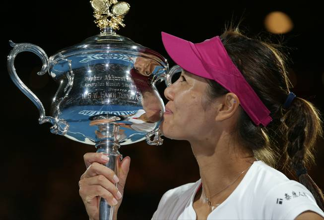 Li Na of China kisses the championship trophy after defeating Dominika Cibulkova of Slovakia in their women's singles final at the Australian Open tennis championship in Melbourne, Australia, on Saturday, Jan. 25, 2014.