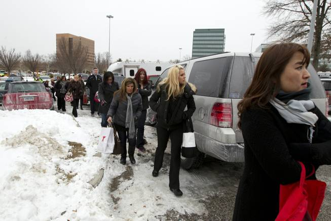 People are evacuated from the Mall in Columbia, Md., after a shooting Saturday Jan. 25, 2014, in Howard County, Md. Police say three people died, including the presumed gunman.