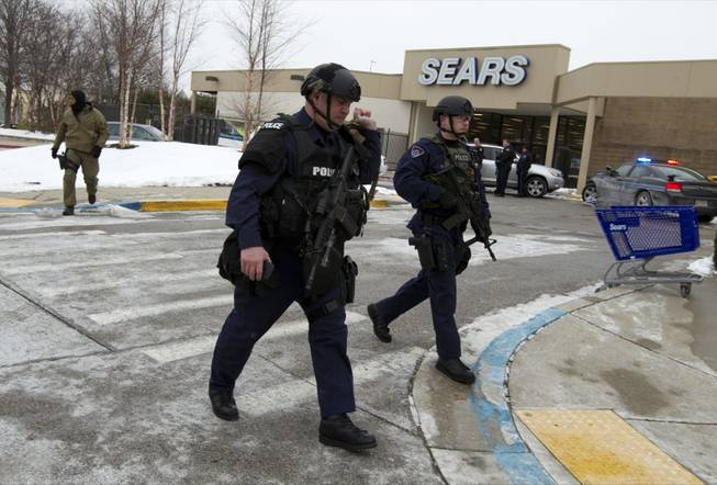 Police move in from a parking lot to the Mall in Columbia after reports of a multiple shooting Saturday Jan. 25, 2014, in Howard County, Md.